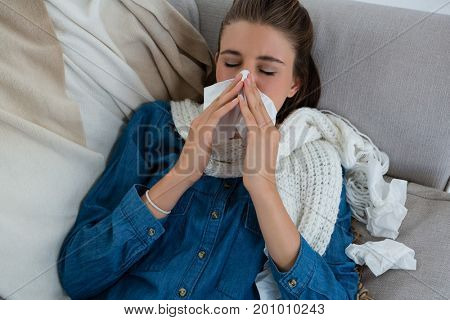 High angle view of woman rubbing nose while lying on sofa at home