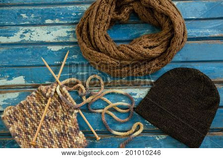 High angle view of muffler with knit hat and knitting needles on wooden table