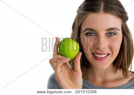 Portrait of smiling woman holding granny smith apple against white background