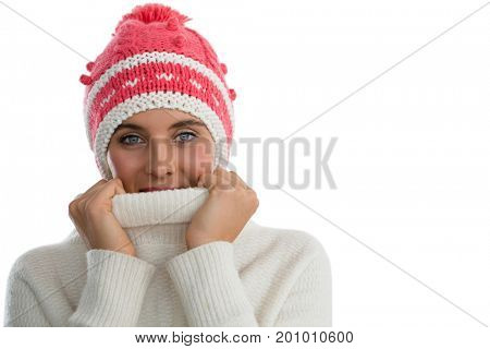 Portrait of woman wearing knit hat while covering face with turtleneck sweater against white background