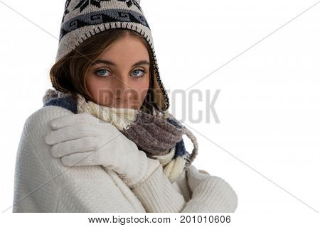 Portrait of young woman hugging self while standing against white background