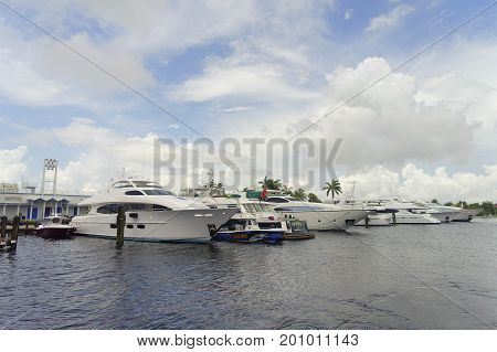 FORT LAUDERDALE, USA - JULY 11, 2017: Some yatchs parket in a raw in a riverwalk promenade, highrise condominium buildings behind, in Fort Lauderdale, Florida.