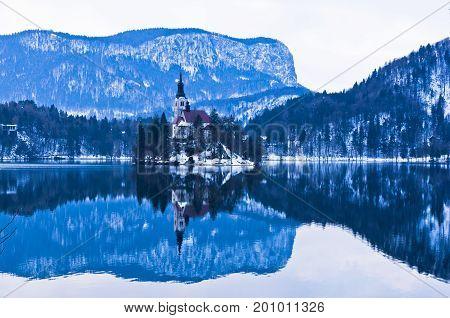 Small island's morning reflection on lake Bled, slovenian Alps, Slovenia