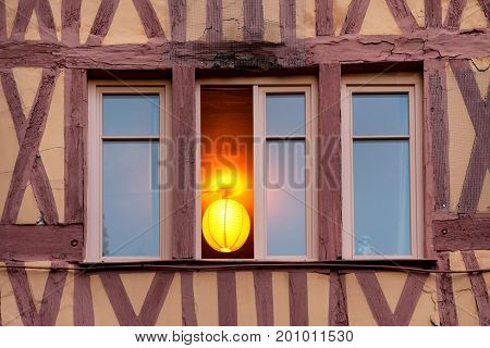 Illuminated window of old timerframe historic house in Rouen, France