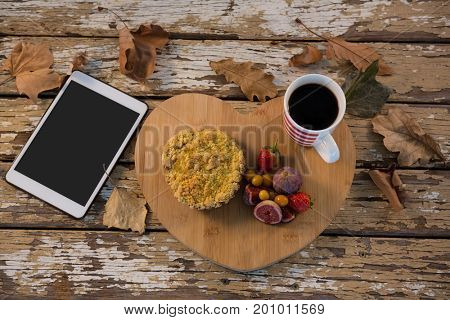 Overhead view of food with coffee cup on wooden tray by tablet computer at table