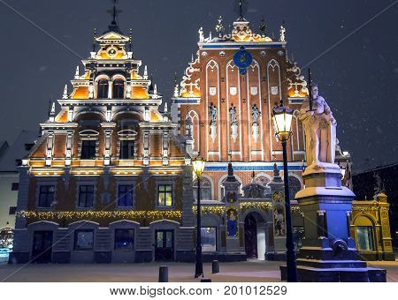LATVIA, RIGA, DECEMBER, 15, 2016 -  House Black-headed with illumination in snowstorm on the eve of Christmas and New Year. Building of 14th century at Town Hall Square. Riga, Latvia