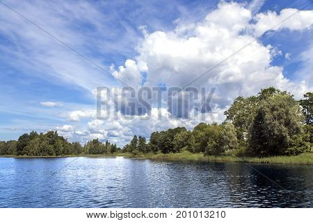 Beautiful summer blue cloudy sky over a clean forest lake in Latvia