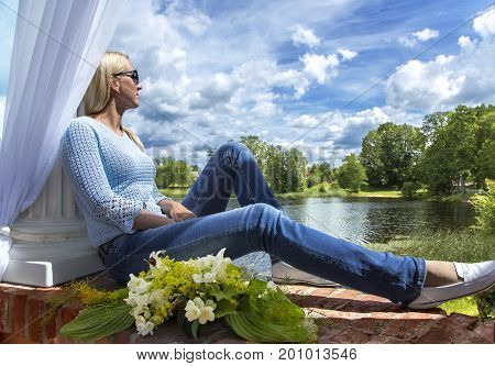 Lovely woman is sitting on the window and looks at the beautiful nature in Birini, Latvia
