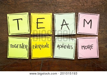 TEAM acronym (together everyone achieves more), teamwork motivation concept, handwriting on a colorful sticky notes against rustic wood