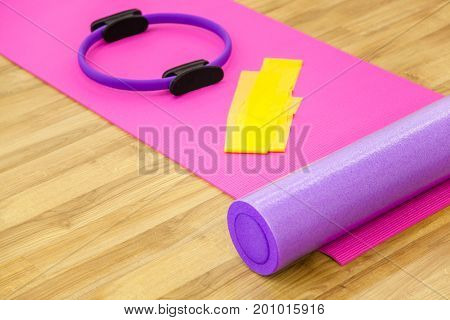 Roller, yoga mat, stability ring and yelow cloth on the parquet. Close-up shot.