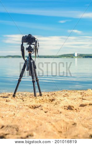 A camera on a tripod on the sandy seashore removes the seascape. Photographic equipment in the process of shooting the landscape. Camera while taking a photo or time-lapse