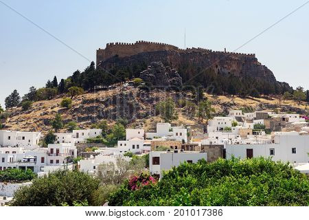 Panoramic view on Lindos town with an  ancient fortress on a hill at Rhodes island, Greece
