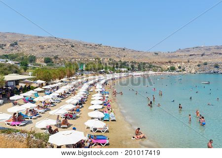 LINDOS, GREECE - AUGUST 2017: People are sunbathing and swimming at Lindos bay on Rhodes island, Greece