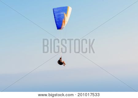 Flying paratrooper with full color parachute, isolated on a blue sky near Rhodes island, Greece
