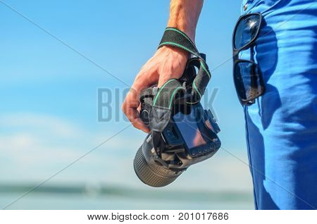 Dslr camera in the hand of a man standing on coast and looking for the story. Dslr camera in a man's hand close-up against a sea horizon