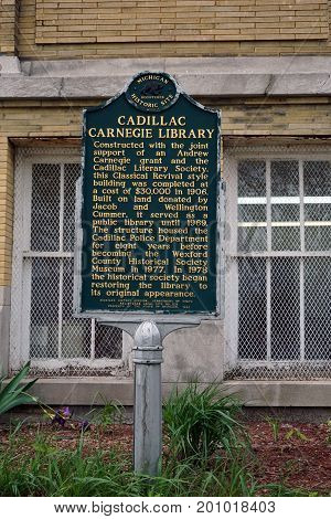 CADILLAC, MICHIGAN / UNITED STATES - MAY 31, 2017: A sign, placed by Department of State's Michigan History Division, describes the historical significance of The historic Cadillac Carnegie Library building, which now houses the Wexford County Historical