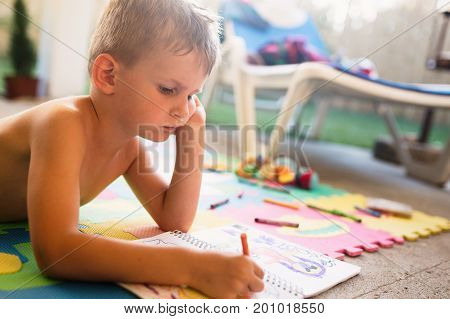 Picture of little boy drawing with crayons on floor