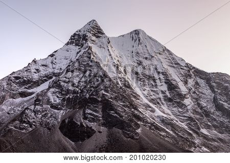 Beautiful Mountain Peak In Snow Lit By Pink Sunrise Light. Morning View Of A Snowy Mountain Peak In