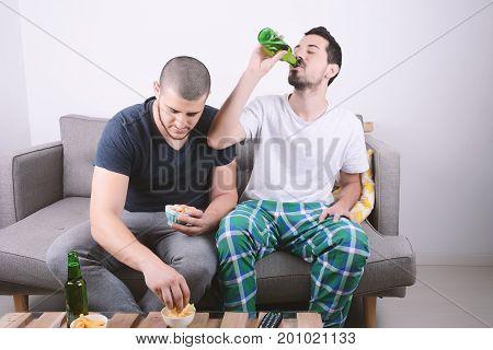 Friends Eating Snacks And Drink Beer.