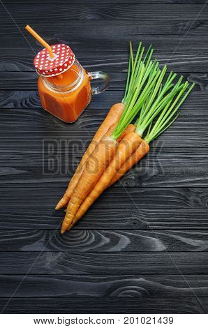 Healthy carrot smoothie in a jar with a red lid in a white polka dots and an orange straw and carrots on black wooden table top view. Healthy food background concept