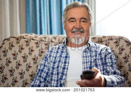 Portrait of smiling senior man operating remote while sitting on sofa in nursing home