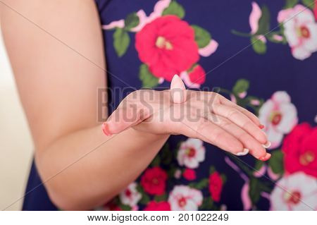Close up of a woman hand, holding in her open hand a soft gelatin vaginal tablet or suppository, treatment of diseases of the reproductive organs of women and prevention of women's health.