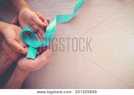 Adult and child hands holding Teal Ribbon toning background Ovarian Cancer cervical Cancer Kidney Cancer and sexual assault awareness