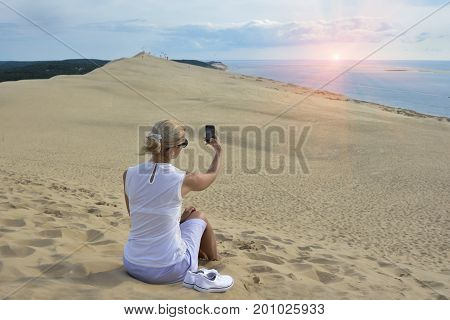 Blonde girl making selfie for instagram at Pyla dune, the largest sand dune in Europe, France