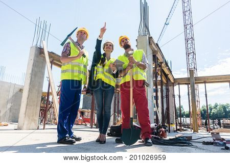 Low-angle view of a visionary architect pointing up while guiding and motivating two workers on the construction site of a new daring project