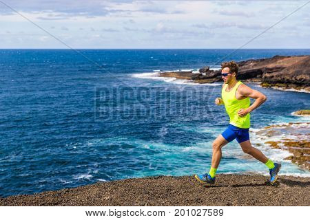 Trail runner athlete man ultra running on rocky trail path with ocean water nature landscape. Active lifestyle of training in nature.