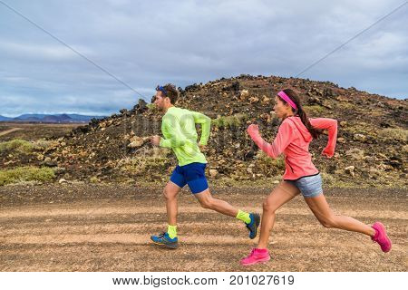 Trail run race ultra runners athletes couple running in rock path in nature landscape. Ultra runner people competing on cross country competition working out endurance on volcanic rocks outdoors