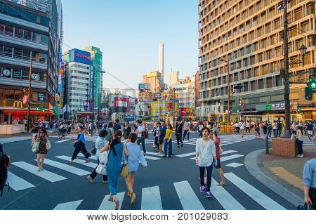 TOKYO, JAPAN JUNE 28 - 2017: Unidentifies people crossing the street using the crosswalk at Ikebukuro district of Tokyo metropolis, Japan. Tokyo Metropolis is both the capital and most populous city of Japan.