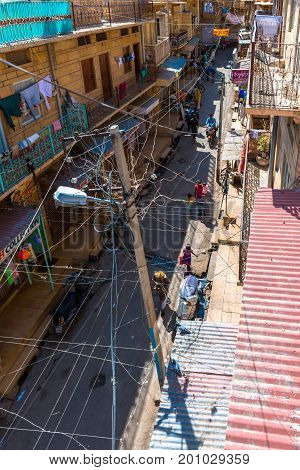 JAISALMER RAJASTHAN INDIA - MARCH 06 2016: From the rooftop of Saalam Singh Ki Haweli normal street in Jaisalmer known as Golden City in India.