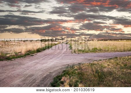 Sun reflecting off the clouds as it rises over an empty dirt road in the prairie.