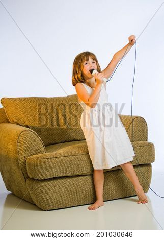 A little girl having fun singing into a microphone at home.