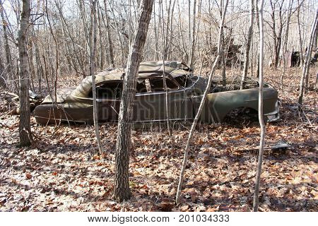 An old rusty car abandoned in the woods for decades