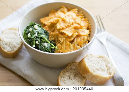 Pasta with white cashew based sauce and red tomatoes sauce with sauteed spinach