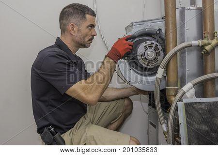 Hvac technician installing a blower motor into a heat pump hvac system.