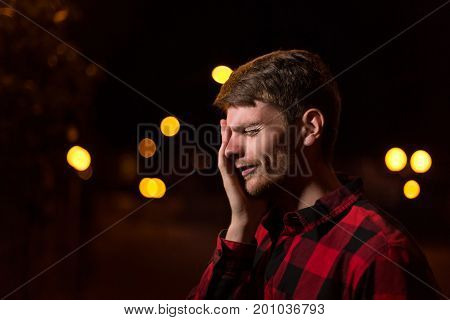 Night portrait of a hipster man. The guy is upset. He is dressed in a plaid shirt. Night city lights in the background