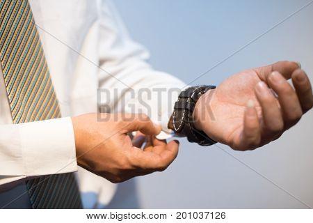 Handsome groom wears a wedding cufflinks preparing for his wedding. Business man dressing just before work in office