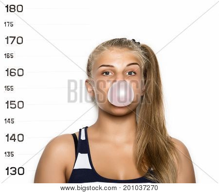Young beautiful blonde woman chewing gum and blowing bubbles Criminal Mug Shots.