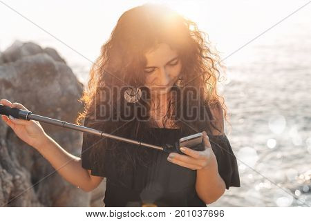 beautiful young woman taking selfie on the beach at sunset