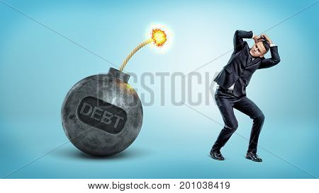 A scared businessman hides his head from a large lit iron bomb with a lettering DEBT. Financial year results. Loans and debts. Business credit.