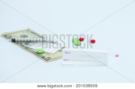 Two methamphetamine cassette test and plastic dropper with red pink and green drugs fake heroin powders american dollar bills and syringe and needle on white background with copy space