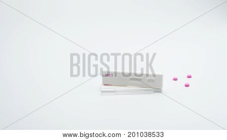 Two methamphetamine cassette test and plastic dropper with pink drugs on white background with copy space