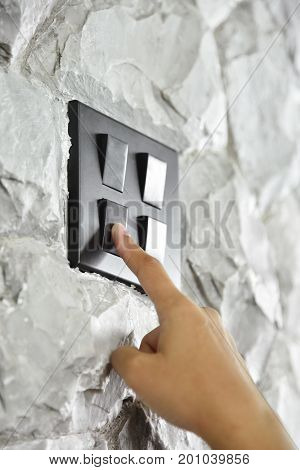 Close up hand turning on or off on grey or black lighting switch on rough stone wall.