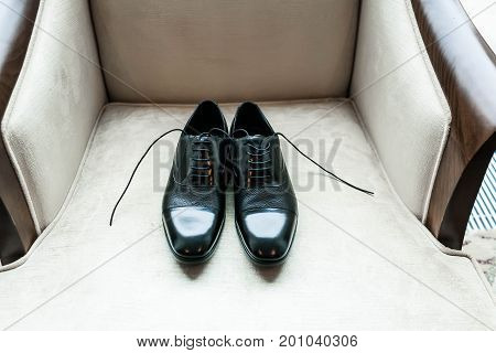 Black Lacquered Shoes Of Groom Lie On A Luxury Armchair. Close-up