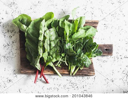 Fresh garden herbs - chard arugula spinach on a wooden cutting board on a light background top view