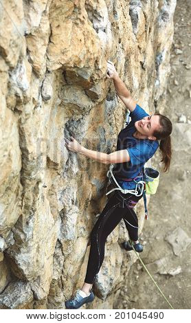 adult woman rock climber. rock climber climbs on a rocky wall. woman makes hard move
