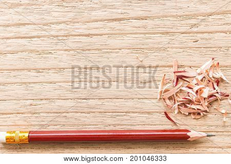 The brown pencil was sharpened on a wooden board